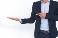 Hombre de negocios con el brazo hacia fuera en un gesto que da la bienvenida Fotos de archivo libres de regalías