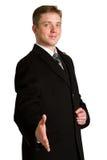 Hombre de negocios con el brazo hacia fuera en un gesto que da la bienvenida, aislado en wh Imágenes de archivo libres de regalías