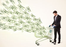 Hombre de negocios con el carro de la compra con los billetes de dólar Imagen de archivo libre de regalías