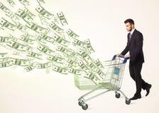 Hombre de negocios con el carro de la compra con los billetes de dólar Fotografía de archivo
