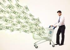 Hombre de negocios con el carro de la compra con los billetes de dólar Foto de archivo libre de regalías