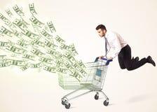 Hombre de negocios con el carro de la compra con los billetes de dólar Fotografía de archivo libre de regalías