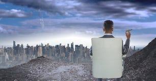 hombre de negocios con el cigarro en asiento en paisaje urbano foto de archivo