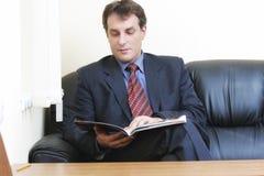 Hombre de negocios con el compartimiento que se sienta en el sofá Fotos de archivo libres de regalías
