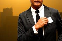 Hombre de negocios con el compuesto de la tarjeta de presentación con el fondo de la luz de la ciudad Imagen de archivo