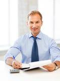 Hombre de negocios con el cuaderno y la calculadora Imagen de archivo