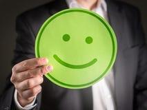 Hombre de negocios con el emoticon sonriente de la cara de la cartulina feliz imagenes de archivo