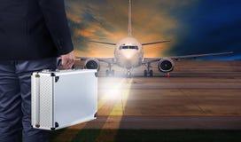 Hombre de negocios con el equipaje fuerte del metal que se coloca en runwa del aeropuerto foto de archivo