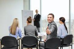 Hombre de negocios con el equipo que muestra los pulgares para arriba en oficina fotografía de archivo libre de regalías