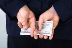 Hombre de negocios con el finger cruzado sosteniendo billetes de banco Foto de archivo