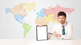 Hombre de negocios con el fondo colorido del mapa del mundo Imagenes de archivo