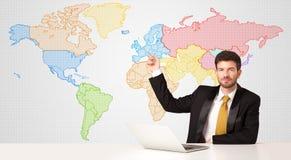 Hombre de negocios con el fondo colorido del mapa del mundo Foto de archivo libre de regalías
