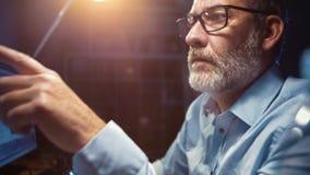 Hombre de negocios con el funcionamiento de vidrios centrado en oficina en la noche imagen de archivo libre de regalías