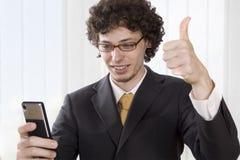 Hombre de negocios con el givig del teléfono móvil pulgares para arriba Fotografía de archivo libre de regalías