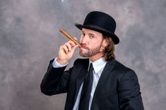 Hombre de negocios con el hongo en el traje negro que fuma el cigarro grande Fotografía de archivo