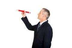 Hombre de negocios con el lápiz rojo grande Imagen de archivo libre de regalías