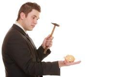 Hombre de negocios con el martillo alrededor para romper la hucha Imagen de archivo libre de regalías