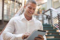 Hombre con el ordenador de la tableta en el edificio moderno del negocio Fotos de archivo