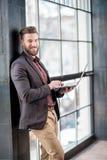 Hombre de negocios con el ordenador portátil cerca de la ventana Imágenes de archivo libres de regalías
