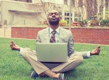 Hombre de negocios con el ordenador portátil que medita en la actitud del loto que toma una respiración profunda foto de archivo