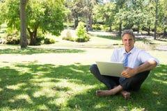 hombre de negocios con el ordenador portátil que se sienta en hierba Imagen de archivo