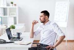 Hombre de negocios con el ordenador portátil y el cuaderno en la oficina Fotos de archivo