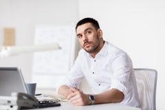 Hombre de negocios con el ordenador portátil y el cuaderno en la oficina Imágenes de archivo libres de regalías