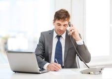 Hombre de negocios con el ordenador portátil y el teléfono Imagen de archivo libre de regalías