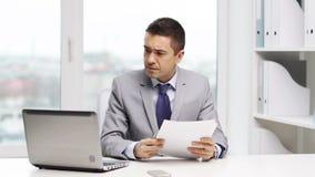 Hombre de negocios con el ordenador portátil y los papeles metrajes