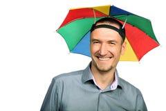 Hombre de negocios con el paraguas del sombrero del arco iris Foto de archivo