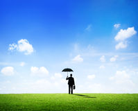 Hombre de negocios con el paraguas que se coloca en un campo Imagen de archivo libre de regalías