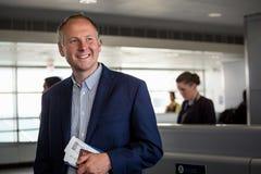 Hombre de negocios con el pasaporte y documento de embarque en el aeropuerto Foto de archivo libre de regalías
