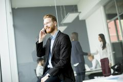 Hombre de negocios con el pelo del jengibre usando el teléfono móvil mientras que el otro busi Fotografía de archivo libre de regalías