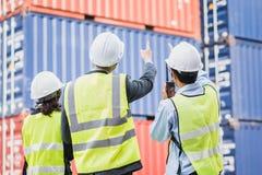 Hombre de negocios con el personal en logístico, exportación, industria de la importación comprobando el envase del buque mercant fotografía de archivo libre de regalías