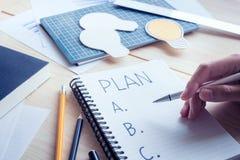 Hombre de negocios con el plan a, b, c de la escritura de la pluma en el cuaderno Fotografía de archivo