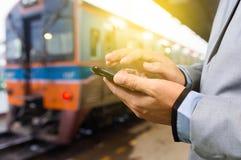 Hombre de negocios con el smartphone, esperando en la plataforma del tren Foto de archivo libre de regalías