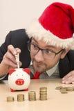 Hombre de negocios con el sombrero de Papá Noel que inserta un billete de dólar en la hucha Imágenes de archivo libres de regalías