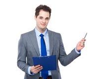 Hombre de negocios con el tablero y la pluma para arriba Fotos de archivo libres de regalías