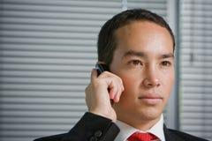 Hombre de negocios con el teléfono celular móvil de la mano Foto de archivo libre de regalías
