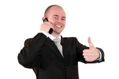 Hombre de negocios con el teléfono celular que presenta con los pulgares para arriba Foto de archivo