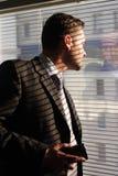 Hombre de negocios con el teléfono que mira a través de persianas de ventana imagen de archivo