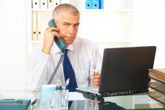 Hombre de negocios con el teléfono y la computadora portátil fotografía de archivo libre de regalías