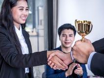 Hombre de negocios con el trabajo en equipo en meta y trofeo que muestra acertado y recompensado por en la oficina imagenes de archivo