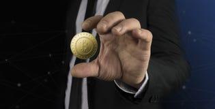 Hombre de negocios con el traje negro que lleva a cabo el bitcoin a mano Fotos de archivo libres de regalías