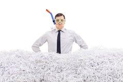 Hombre de negocios con el tubo respirador que se coloca en papel destrozado imagenes de archivo