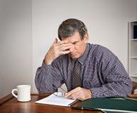 Hombre de negocios con exceso de trabajo, cansado en el escritorio Fotografía de archivo libre de regalías