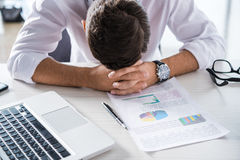 Hombre de negocios con exceso de trabajo y cansado que se sienta en el lugar de trabajo con el ordenador portátil y las cartas Imagenes de archivo