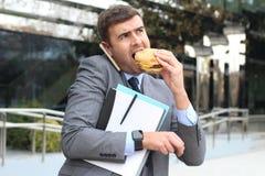 Hombre de negocios con exceso de trabajo que come los alimentos de preparación rápida en camino imagenes de archivo