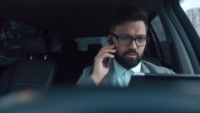 Hombre de negocios con la barba que habla en el teléfono y que mira la tableta almacen de metraje de vídeo