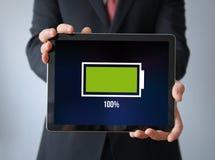 Hombre de negocios con la batería llena en una tableta Fotos de archivo libres de regalías